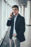 Biznesmen rozmowa telefon komórkowy i spojrzenie na kamerze w biurze Zdjęcie Stock