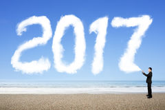 Biznesmen rozpyla biel 2017 rok chmury kształt w niebie Zdjęcie Royalty Free