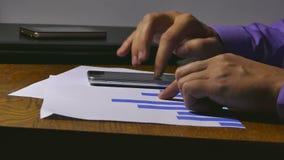 Biznesmen rozważa smartphone mienia mapy analityka dokumentów sprzedaże zdjęcie wideo