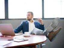Biznesmen rzucał jego nogi na biurku relaksować Zdjęcia Stock