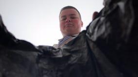 Biznesmen rzuca zmięte plastikowe butelki w grat Widok z wewnątrz kosza zbiory