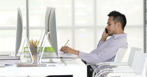 Biznesmen siedzi przed komputerami zdjęcie wideo