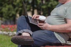Biznesmen siedzi przy parkiem i używa laptop Biznesmen używa laptop plenerowego Obrazy Stock