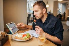 Biznesmen siedzi przy stołem i je posiłek od talerza Kawałek pomidor na rozwidleniu Facet jest przyglądającym pastylką Zdjęcie Royalty Free