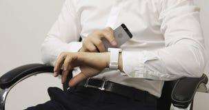 Biznesmen siedzi w biurowym krześle i używa dotyka ekran na smartphone zbiory