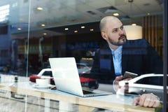 Biznesmen siedzi w kawiarni z laptopem i czeka prawnika dla zatwierdzenia urzędowi dokumenty Zdjęcia Royalty Free