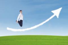 Biznesmen skacze nad sukces strzała znaka chmurą Fotografia Royalty Free
