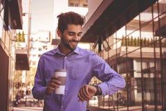 Biznesmen sprawdza czas outdoors człowiek na zegarek obraz royalty free