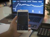 Biznesmen sprawdza rynek papierów wartościowych na wiszącej ozdobie obraz royalty free