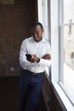 Biznesmen Sprawdza telefon pozycję Biurowym okno zdjęcie stock