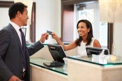 Biznesmen Sprawdza Wewnątrz Przy Hotelowym Recepcyjnym Frontowym biurkiem fotografia royalty free