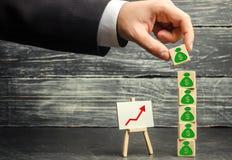 Biznesmen stawia blok z obrazkiem dolary Pomyślny biznes i Narosły budżet i zyski zdjęcie royalty free