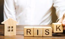 Biznesmen stawia drewnianych bloki z słowa ryzykiem i domem Nieruchomości inwestorski ryzyko ryzykowne inwestycje Strata własność zdjęcia royalty free