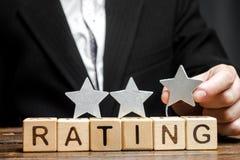 Biznesmen stawia trzeci gwiazdę nad słowo ocena na drewnianych blokach Pojęcie ilość usługa Hotel lub restauracja zdjęcie stock