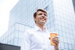 Biznesmen stoi blisko centrum biznesu i pije kawę zdjęcia stock