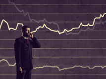 Biznesmen stoi nad diagrama tłem z smartphone Bu Zdjęcia Stock