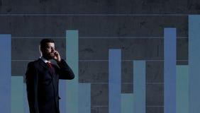 Biznesmen stoi nad szpaltowego diagrama backgro z smartphone Fotografia Stock