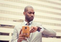 Biznesmen texting na telefonie komórkowym i patrzeje jego zegarek Zdjęcie Stock