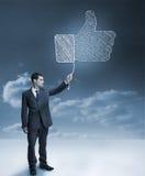 Biznesmen trzyma błękitnego gigantycznego kciuk up Zdjęcia Royalty Free