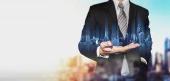 Biznesmen trzyma błękitnego hologram nowożytni budynki z plamy tłem i kopii przestrzenią, Zdjęcia Royalty Free