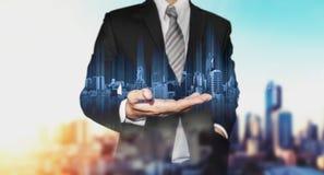 Biznesmen trzyma błękitnego nowożytnego budynku hologram na ręce, z czarny i biały miasta tłem Zdjęcia Royalty Free