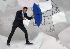 Biznesmen trzyma błękitnego parasol wśród latania tapetuje przeciw graffiti ścianie Fotografia Stock