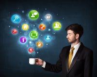 Biznesmen trzyma białą filiżankę z położenie ikonami Obrazy Stock