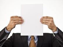 Biznesmen trzyma białego papier przed jego fa obraz royalty free