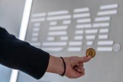 Biznesmen trzyma Bitcoin monetę Slovenia, Luty z IBM logo na laptopu ekranie, - 26th, 2019 fotografia royalty free