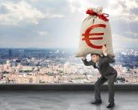 Biznesmen trzyma ciężkiego moneybag z euro znakiem zdjęcie stock