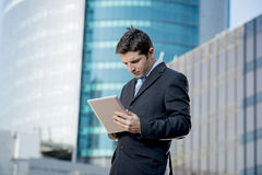 Biznesmen trzyma cyfrową pastylkę stoi outdoors pracować dzielnicy biznesu Fotografia Stock