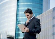 Biznesmen trzyma cyfrową pastylkę stoi outdoors pracować outdoors dzielnicy biznesu Fotografia Royalty Free
