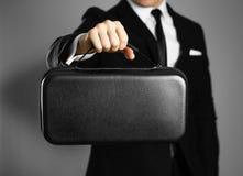 Biznesmen trzyma czarną rzemienną torbę w czarnym kostiumu z bliska Odosobniony tło obrazy royalty free