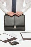 Biznesmen trzyma czarną teczkę i pozycję blisko pracy Zdjęcie Royalty Free