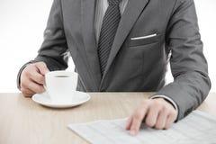 Biznesmen trzyma czytanie i filiżankę kawy gazeta Zdjęcie Royalty Free