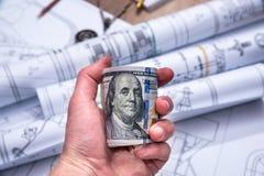 Biznesmen trzyma dolary nad rysunkowa maszyna Zdjęcia Stock