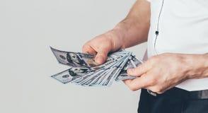Biznesmen trzyma dolary w jego rękach Bogaty człowiek rozważa pieniądze w pokoju fotografia royalty free