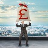 Biznesmen trzyma dużego moneybag z funta znakiem Obrazy Stock