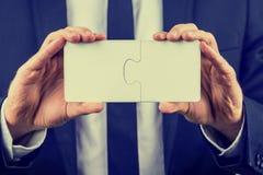 Biznesmen trzyma dwa łączącego łamigłówka kawałka obrazy stock