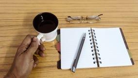 Biznesmen trzyma filiżankę kawy Biznesu kieszeniowy planista z eyeglass i piórem gotowymi zauważać spotkanie Biznes obrazy stock