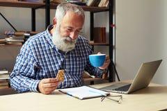 Biznesmen trzyma filiżankę kawy i ciastka Obraz Stock