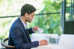Biznesmen trzyma filiżankę podczas gdy używać laptop Obraz Royalty Free