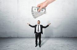Biznesmen trzyma kilka banknoty z przyglądającym up na gigantycznej ręce zdjęcia royalty free