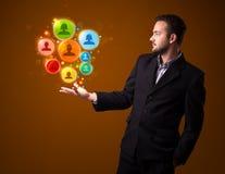 Biznesmen trzyma kolorowe ogólnospołeczne sieci ikony w jego ręka ilustracji