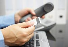 Biznesmen trzyma kredytową kartę i dzwoni banka fotografia stock