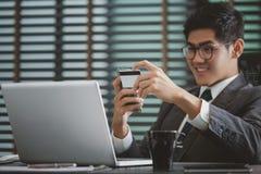 Biznesmen trzyma kredytową kartę i używa mądrze telefon dla online zakupy Obrazy Stock