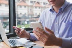 Biznesmen trzyma kredytową kartę & mądrze telefon przy biurem mężczyzna pur Zdjęcia Royalty Free