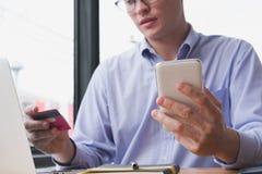 Biznesmen trzyma kredytową kartę & mądrze telefon przy biurem mężczyzna pur Obrazy Royalty Free