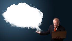 Biznesmen trzyma laptop i przedstawia abstrakt chmury kopię Obrazy Royalty Free