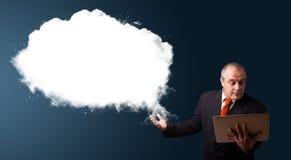 Biznesmen trzyma laptop i przedstawia abstrakt chmury kopię Zdjęcie Stock